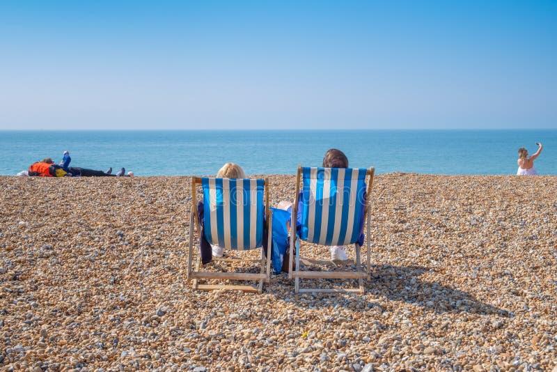 Couple sitting in deckchairs on a beach. stock photos