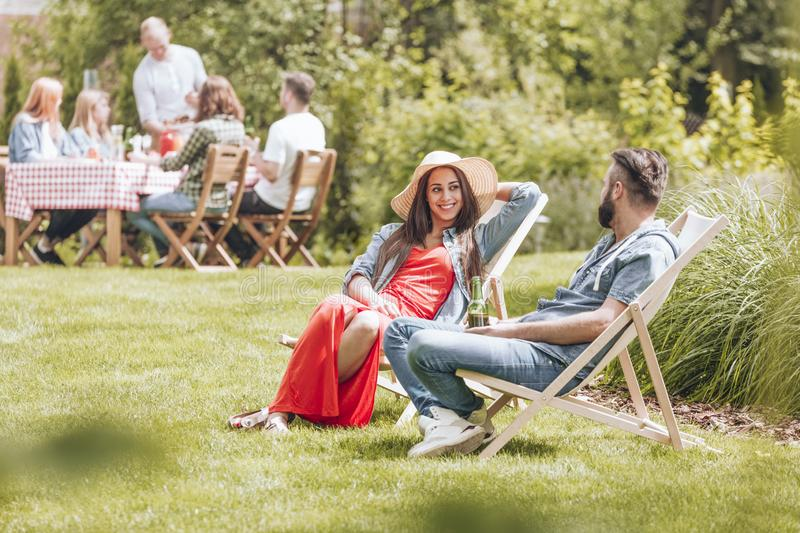 Couple sitting on deckchairs on the grass. People gathered around a picnic table in the garden. stock images