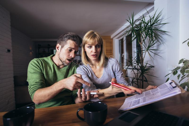 Couple sitting at the desk at home read notice paper check bills or bank account balance royalty free stock photography