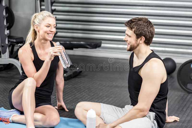 Couple sitting on fitness mat stock image