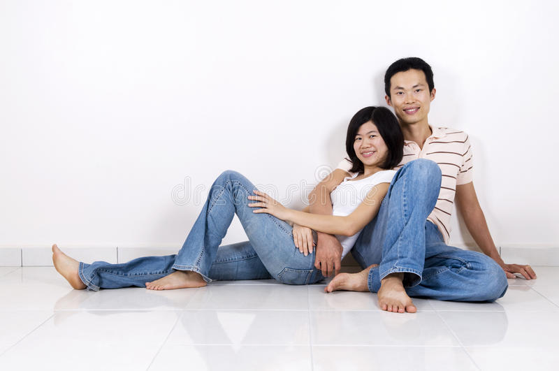 Couple sitting on floor at home. Young Asian adult couple sitting together on tiles floor in home smiling royalty free stock photos