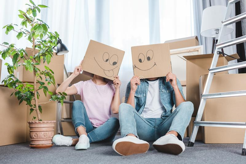 couple sitting on floor after moving into new home with boxes royalty free stock images