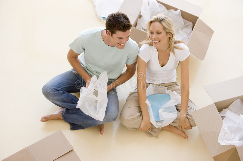 Couple sitting on floor by open boxes in new home stock images