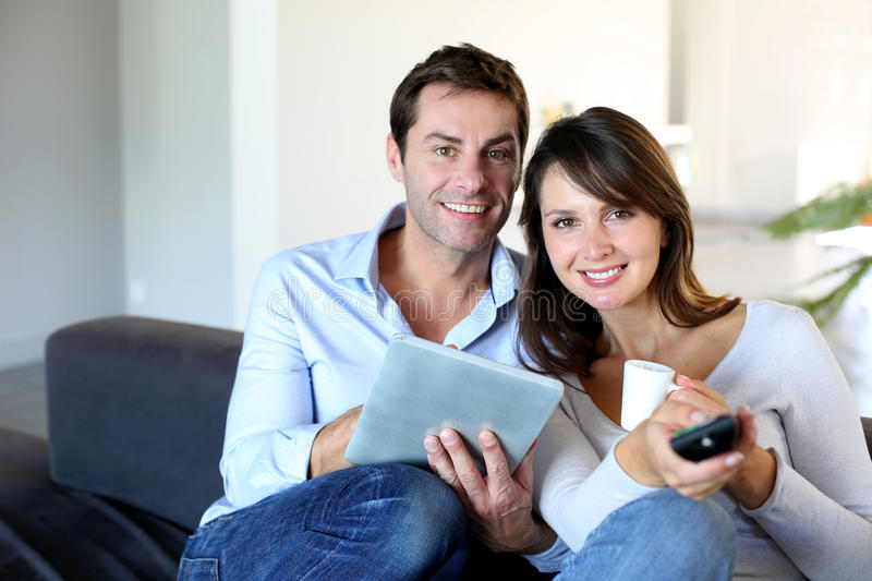 Couple sitting in front of tv set royalty free stock image