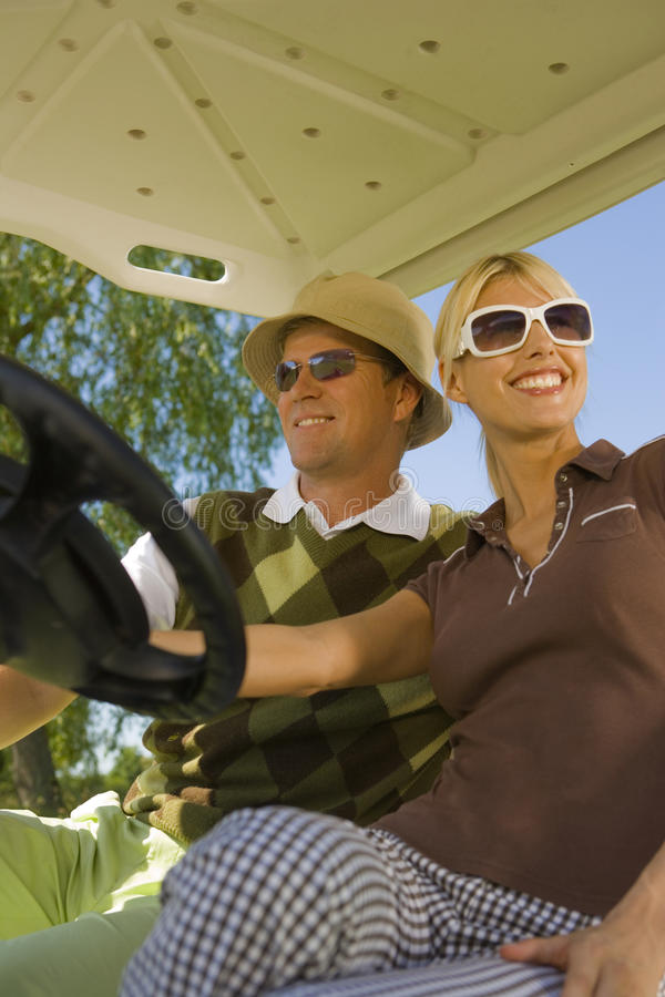 Couple sitting in a golf cart and smiling royalty free stock photography