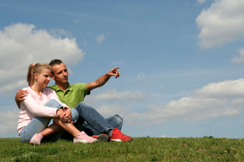 Couple sitting on grass stock image