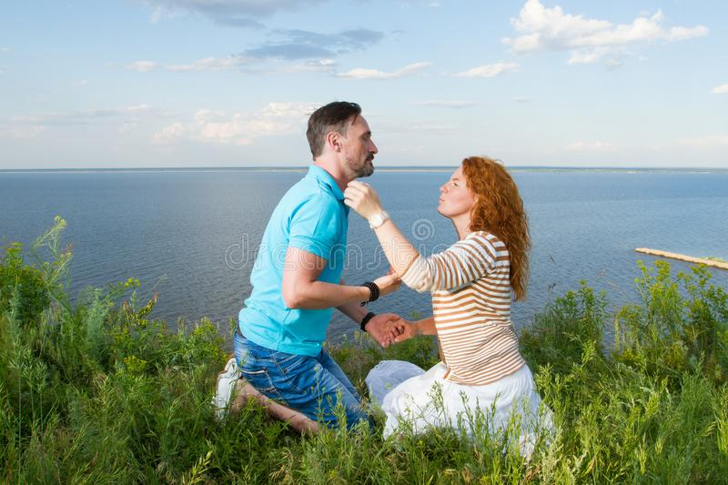 Couple sitting on grass face to face on knees in the grass on sea and sky background. Young couple enjoying outdoors rest. royalty free stock photos