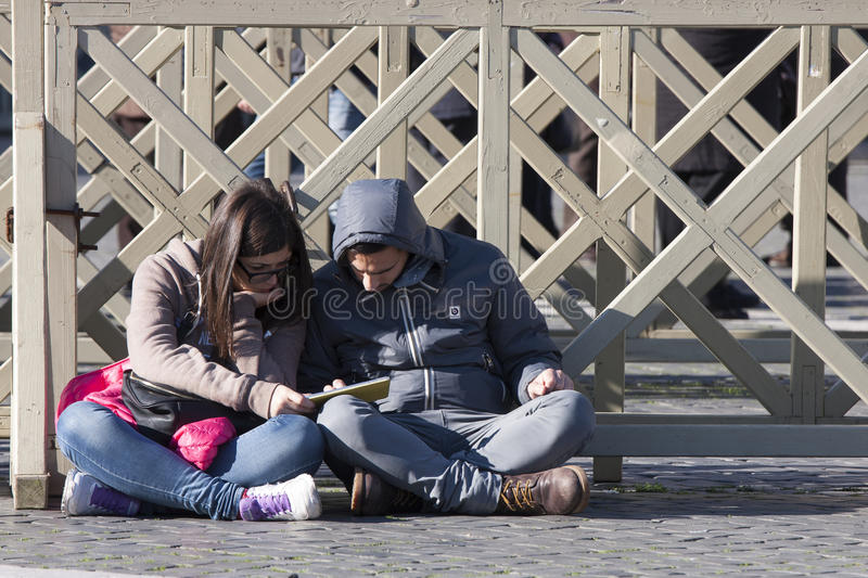 Couple sitting on the ground with a city guide stock photography