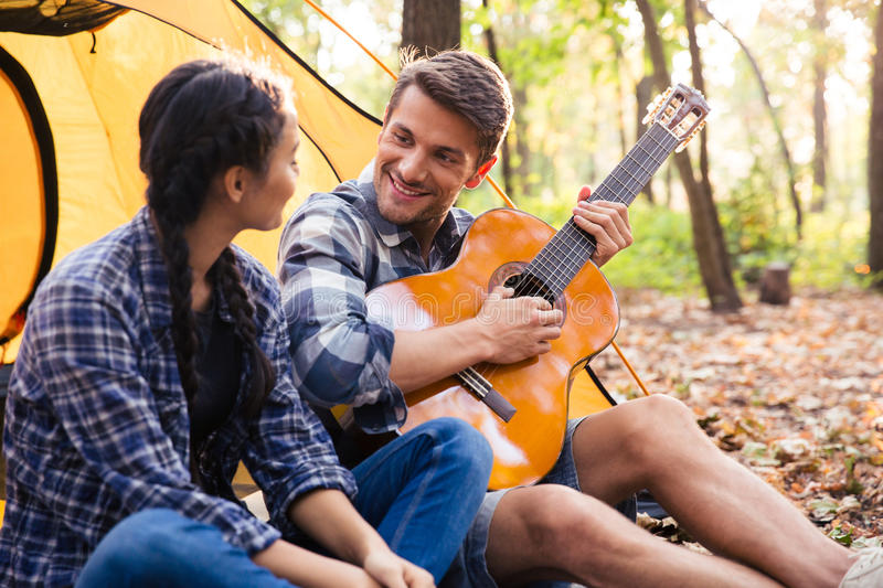 Couple sitting with guitar in the forest stock image