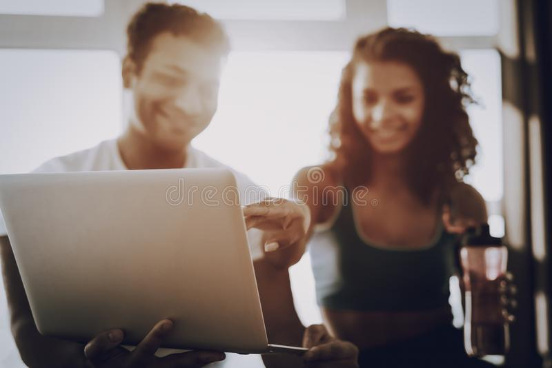 Young Couple Sitting On Gym Carpet With Laptop. A Couple Sitting On Gym Carpet With Laptop. Healthy Lifestyle. Shape Sportswear. Attractive Athlete. Physical stock photography