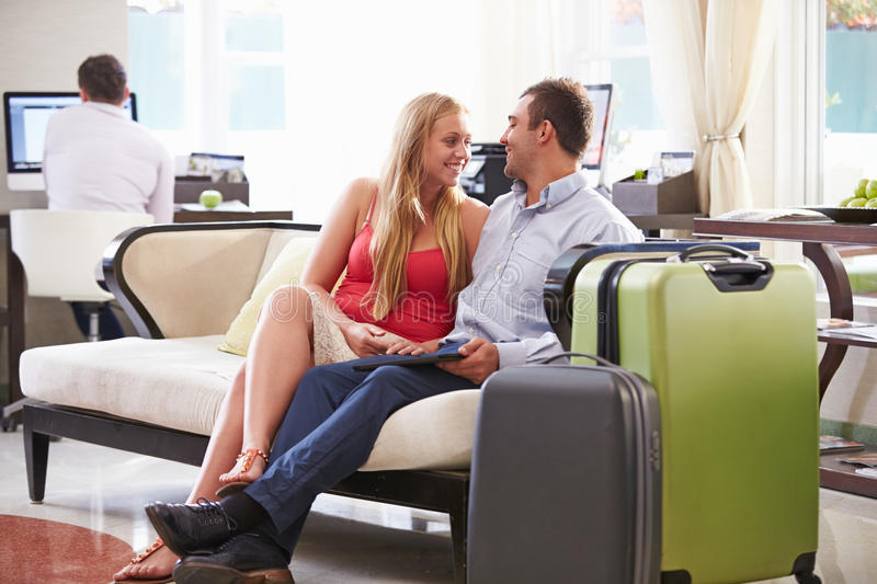 Couple Sitting In Hotel Lobby With Luggage stock photos