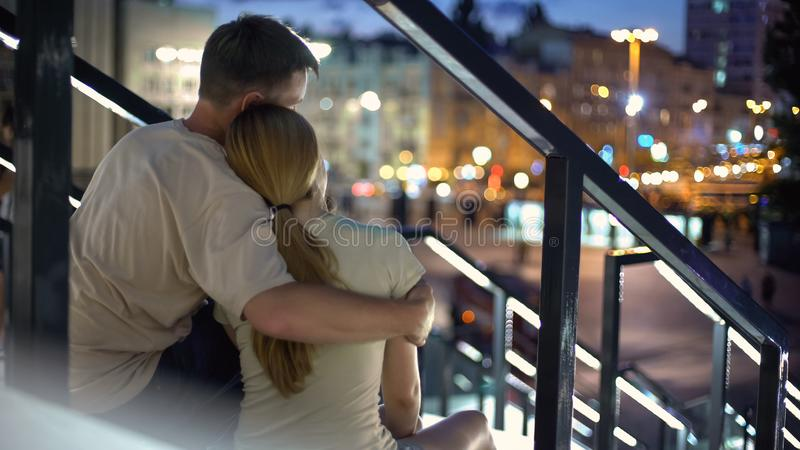 Couple sitting and hugging on stairs, enjoying beautiful city view, romantic stock photo