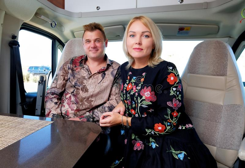 Couple sitting inside of recreational vehicle looking at camera royalty free stock images