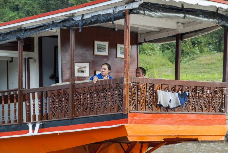 Couple sitting on Laotian longboat stock photography