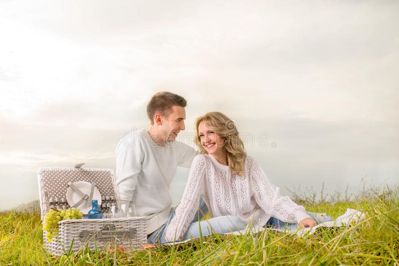 Couple sitting and laughing on a picnic with white basket stock image