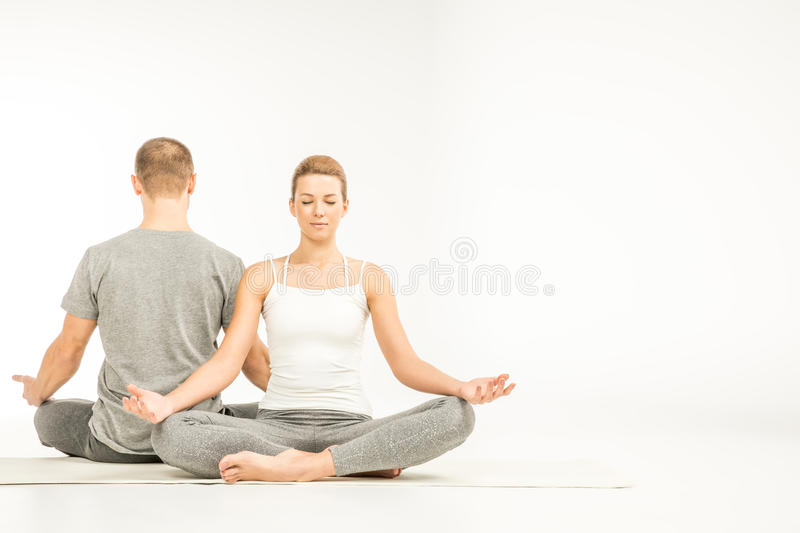 Couple sitting in lotus position. Young couple practicing yoga sitting in lotus position on yoga mats stock image