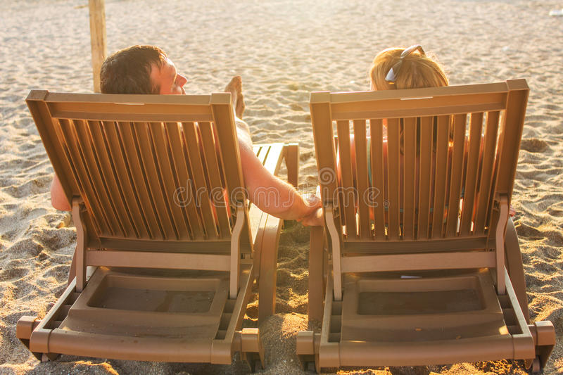 Couple sitting on the lounge chairs stock photo