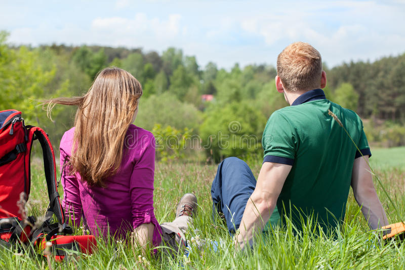 Couple sitting on meadow and looking at the landscape. Back view of a couple sitting on meadow and looking at the landscape royalty free stock images