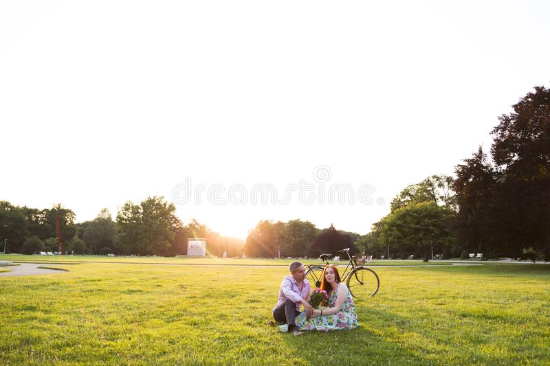 Couple sitting near bicycle at park on summer day stock photography