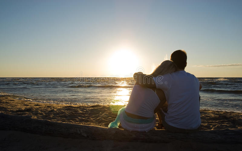 Couple sitting near the sea on sunset royalty free stock photography