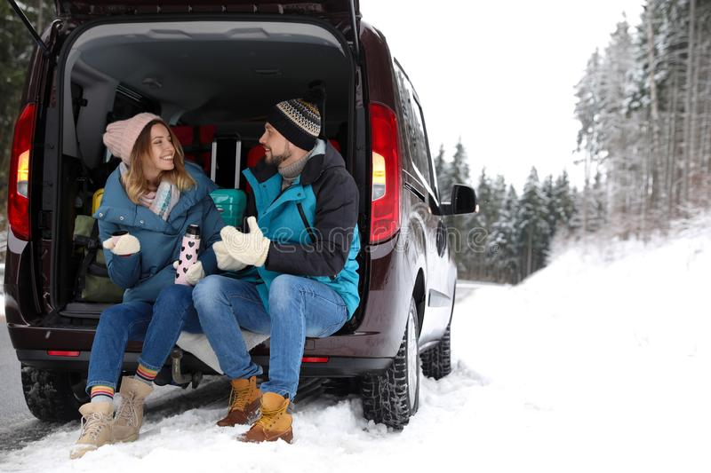 Couple sitting in open car trunk full of luggage near road, space for text. Winter stock photography