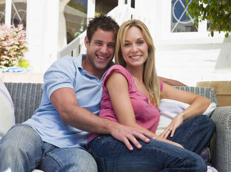 Couple sitting outdoors on patio smiling royalty free stock image