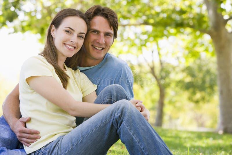 Download Couple Sitting Outdoors Smiling Stock Image - Image of horizontal, camera: 5931503