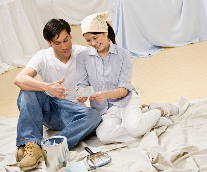 Couple sitting with paint can and color swatch royalty free stock photo