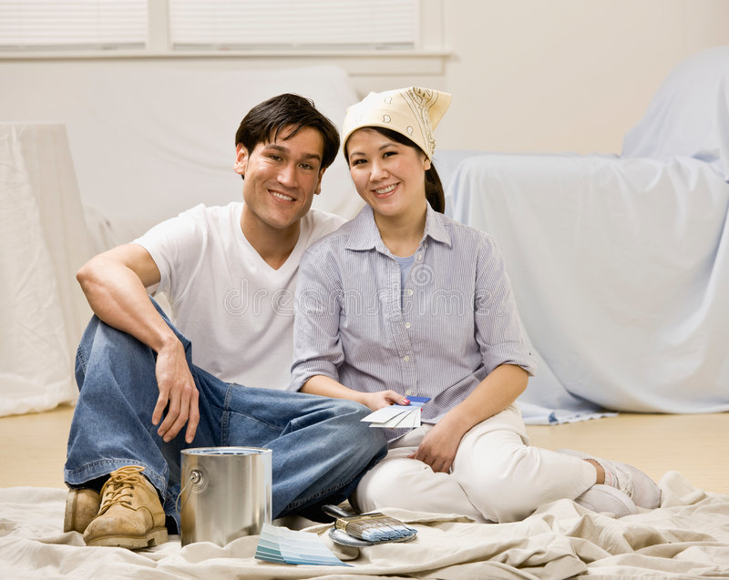 Couple sitting with paint can and paint swatch stock photography