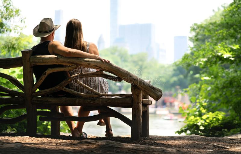 Couple sitting on a park bench and having a romantic first date. Lovers with romance and trust. stock images