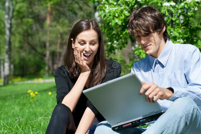 Download Couple Sitting In Park And Using Laptop Stock Image - Image of lifestyles, female: 19539787
