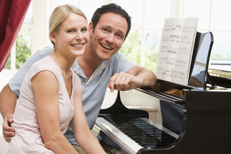 Couple sitting at piano smiling royalty free stock image