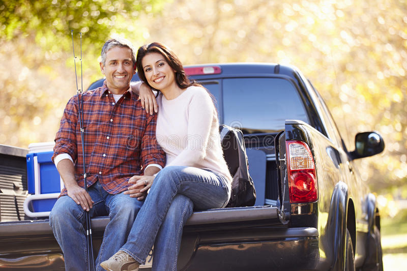 Couple Sitting In Pick Up Truck On Camping Holiday. Happy Couple Sitting In Pick Up Truck On Camping Holiday Smiling royalty free stock images