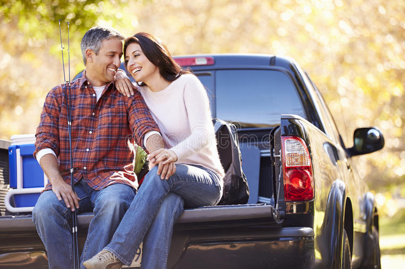 Couple Sitting In Pick Up Truck On Camping Holiday. Holding Hands Smiling stock photo