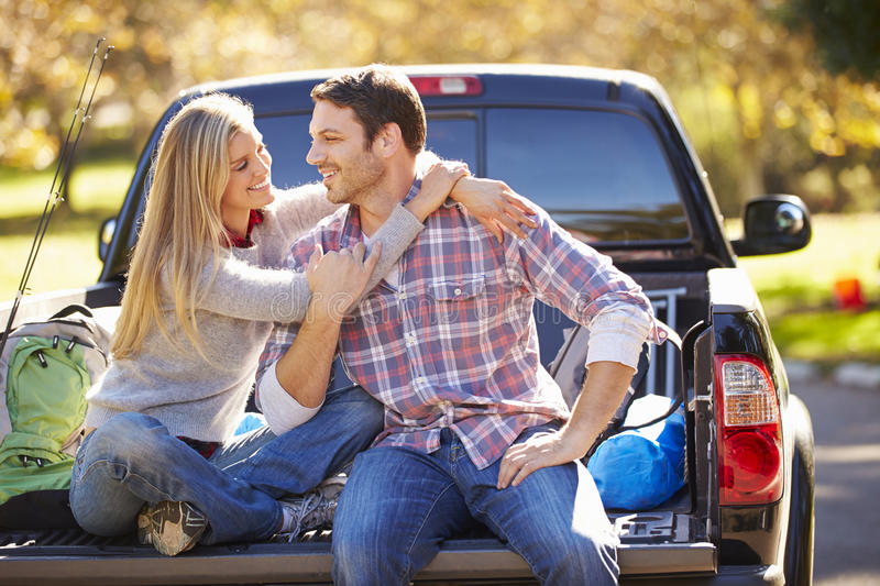Couple Sitting In Pick Up Truck On Camping Holiday. Hugging Each Other royalty free stock photography