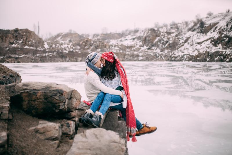 Couple is sitting at rock, embracing and smiling against background of snow-covered hills and frozen lake. Closeup. royalty free stock photo