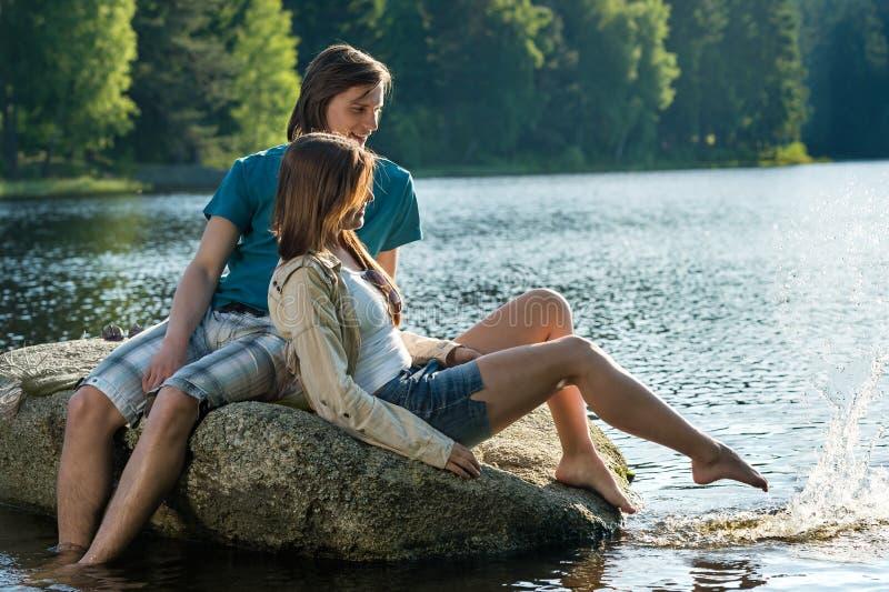 Couple sitting on rock sharing romantic moment stock photos