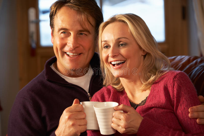 Download Couple Sitting On Sofa With Hot Drinks Watching TV Stock Image - Image: 25640335