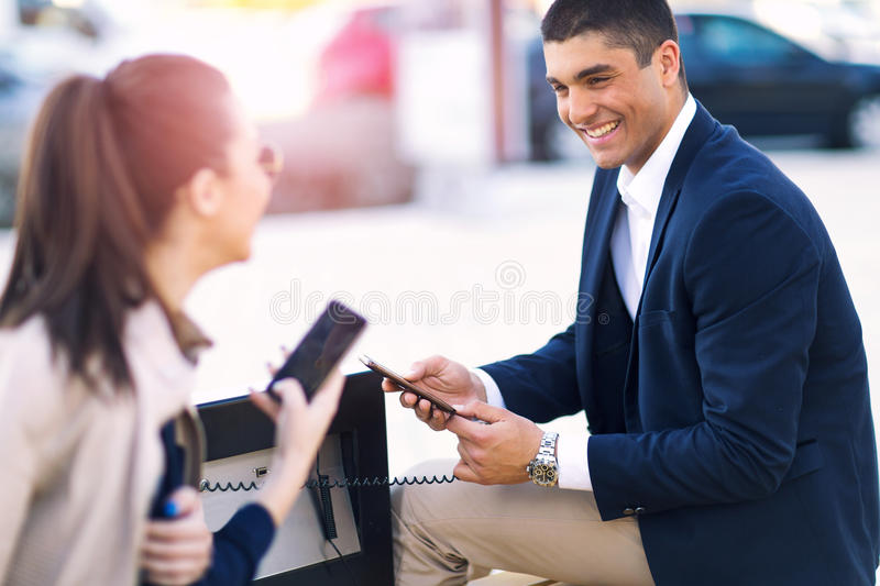 Couple sitting on solar bench and charges phone. Young couple sitting on solar bench and charges phone royalty free stock images
