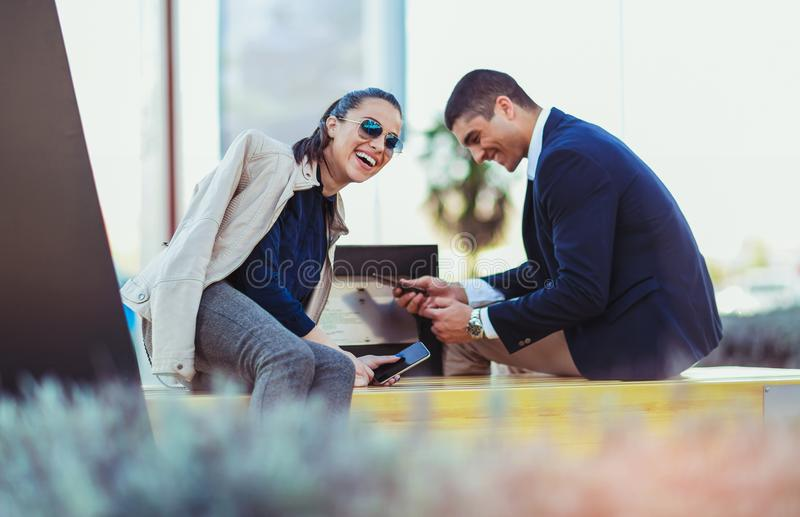 Couple sitting on solar bench and charges phone. Young couple sitting on solar bench and charges phone stock image