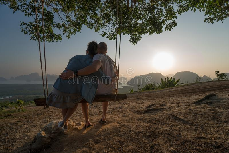 Couple on the bench over beautiful tropical mountain landscape. Couple sitting on the swinging bench over beautiful tropical mountain landscape during sunrise stock photo