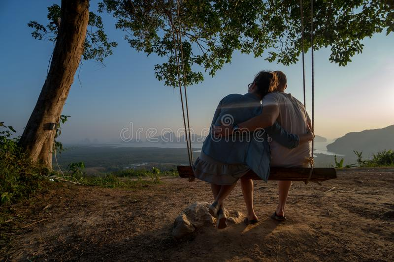 Couple on the bench over beautiful tropical mountain landscape. Couple sitting on the swinging bench over beautiful tropical mountain landscape during sunrise stock photography