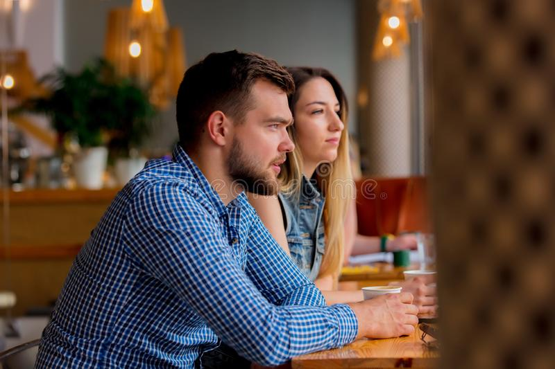 Couple sitting at a table in a cafe and drinking coffee royalty free stock photo