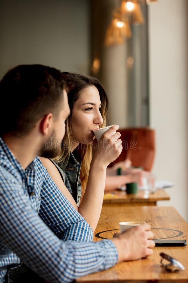 Couple sitting at a table in a cafe and drinking coffee royalty free stock image