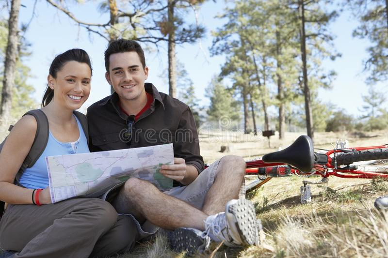 Couple Sitting Together With Roadmap. Portrait of a happy Caucasian couple sitting together with roadmap stock photo
