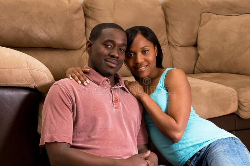 Couple Sitting Together By A Sofa- Horizontal stock photography
