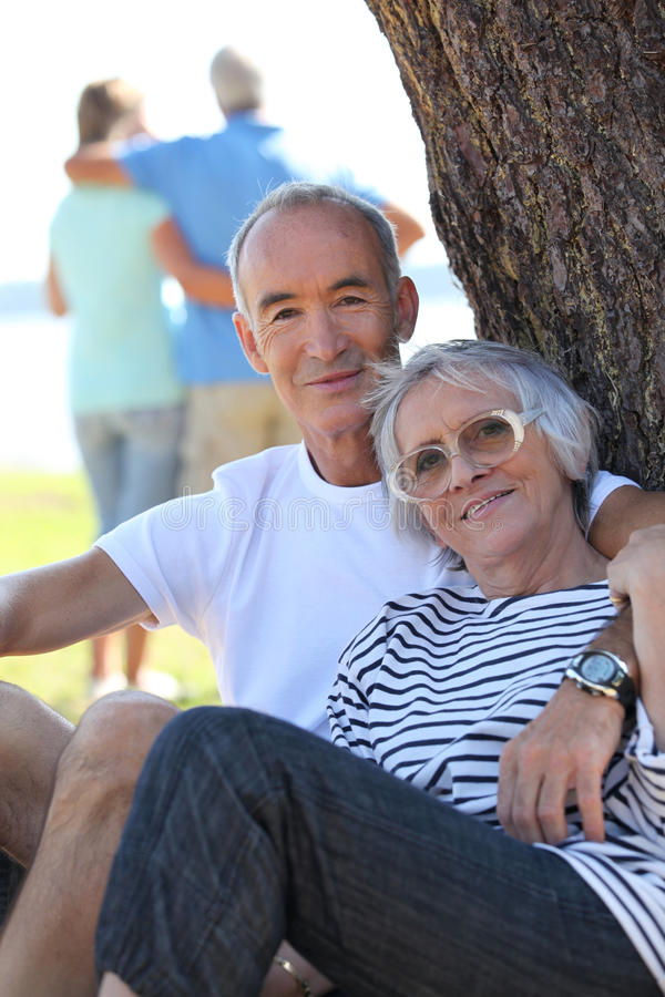 Couple sitting by a tree stock image