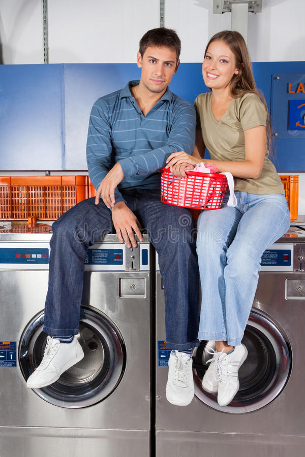 Couple Sitting On Washing Machines royalty free stock image