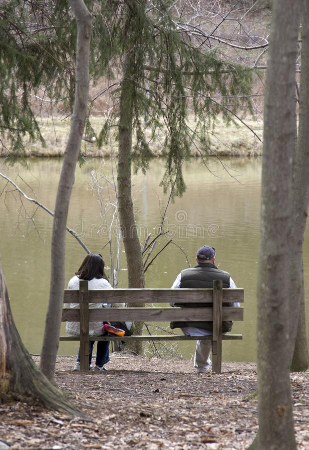 Couple sitting on wooden bench stock images