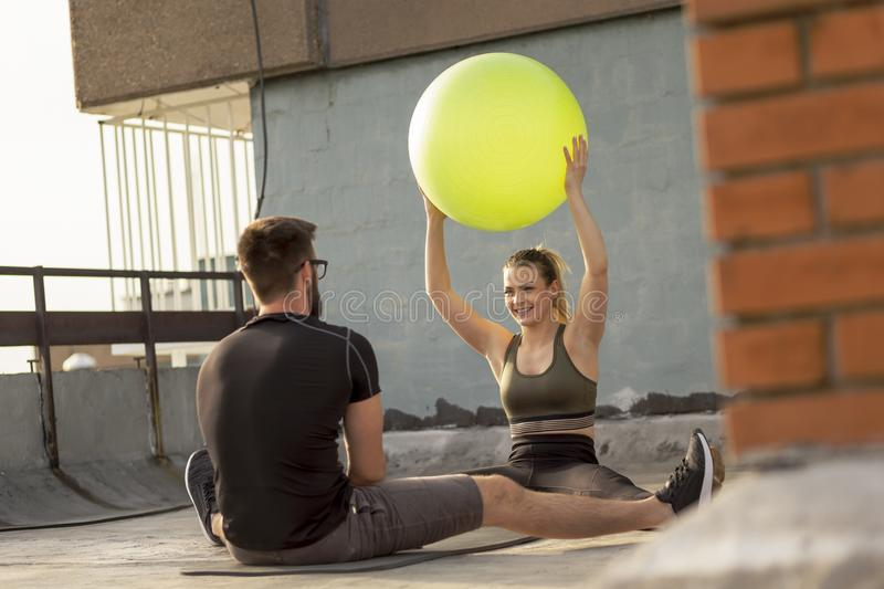 Couple exercising with the pilates ball. Couple sitting on a yoga mat on a building rooftop terrace, exercising with a pilates ball stock photo
